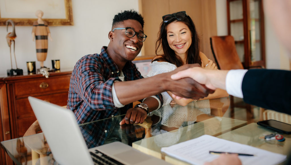 Young couple shaking hands with their lender after getting pre-approved for their home loan.